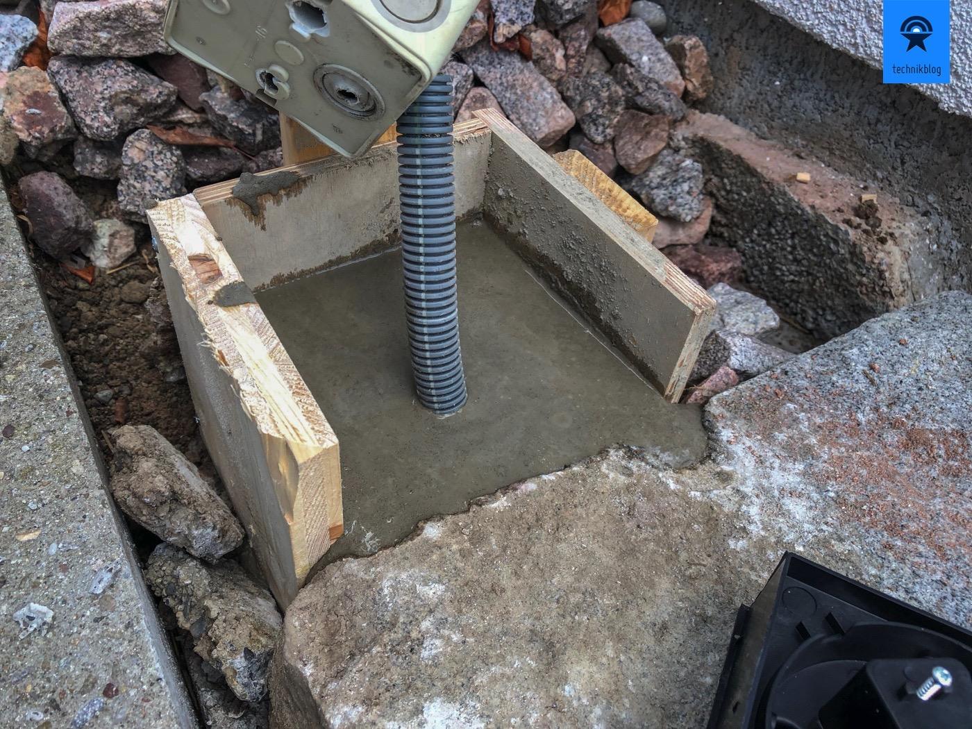 Kleine Schalung für den Betonsockel gebaut, darin Rohr mit Stromkabel verlegt